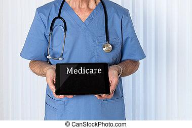 Senior doctor in scrubs facing camera - Senior male...