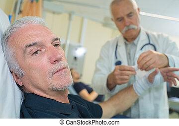 senior doctor putting a bandage on an elder mans arm