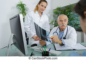 senior doctor showing x-ray to patient in his office