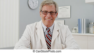 Senior doctor sitting at desk smiling at camera