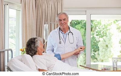 Senior doctor taking the blood pres