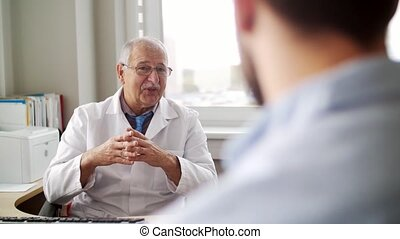 senior doctor talking to male patient at hospital -...