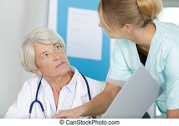 senior doctor talking to nurse