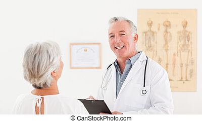 Senior doctor talking with his sick patient
