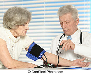 Senior doctor with a elderly patient in his office
