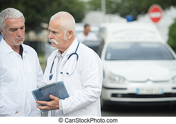 senior doctor with colleague holding clipboard in front of ambulance