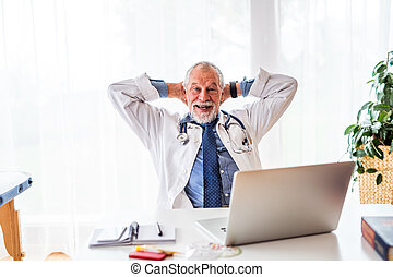 Senior doctor with laptop at the office desk.