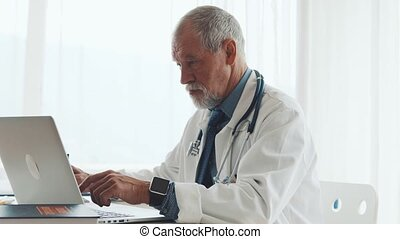 Senior doctor with laptop working at the office desk. -...