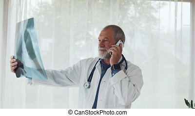 Senior doctor with smartphone looking at x-ray in office.