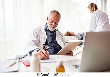 Senior doctor with tablet in his office.