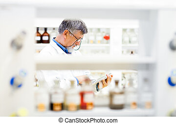 Senior doctor/scientist using his tablet computer at work (color