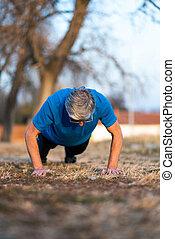 Senior doing pushups on outdoor workout