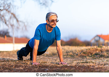 Senior doing pushups on outdoor workout