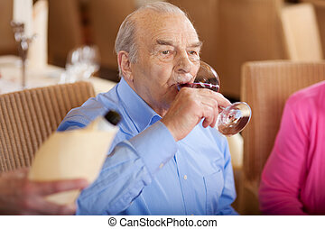 senior drinking a glass of red wine in restaurant
