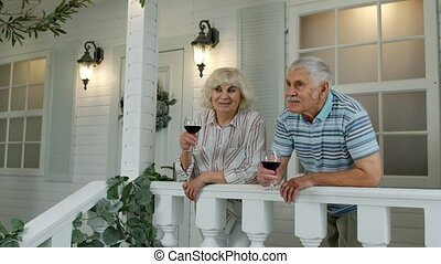 Senior elderly Caucasian couple drinking wine in porch at home. Happy mature retired family resting