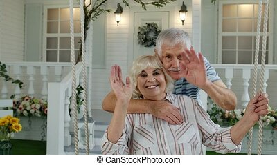 Senior elderly couple in front yard at home. Man hugging woman. Happy mature family waving hands