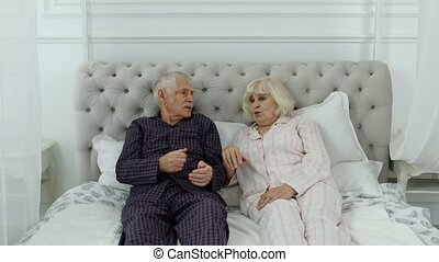 Senior elderly couple wearing pyjamas lying on bed having an argument in bedroom. Mature caucasian grandparents, husband and wife after quarrel turning back to back on bed at home. 6k downscale
