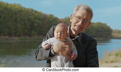 Senior elderly man holding to his baby granddouther, holding him close up, side view.