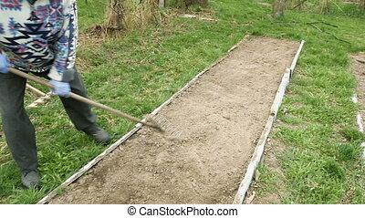 Senior elderly man ploughs plows vegetable garden