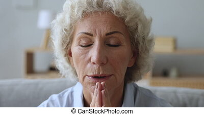 Senior elderly woman praying with hope at home, closeup view...