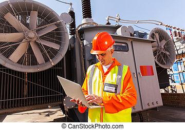 senior electrical technician using laptop computer -...