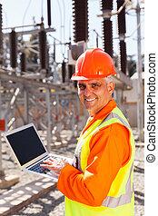 senior electrician using laptop