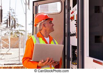 senior electrician working on a transformer