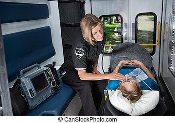 Senior Emergency Care in Ambulance - Female EMT worker...