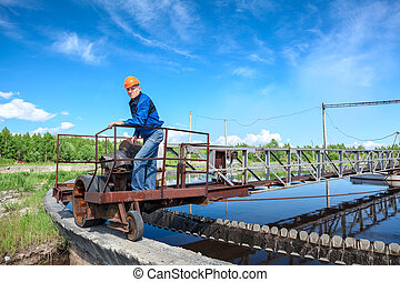 Senior engineer in hardhat standing on waste water treatment unit