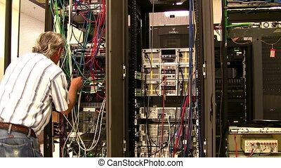 Senior engineer working on server wiring in data center