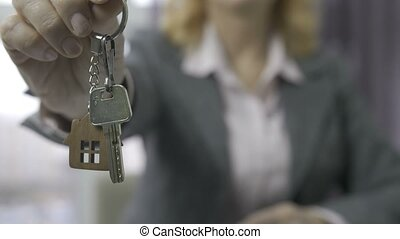 Senior estate agent midsection showing house keys