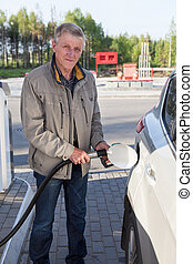 Senior European man filling own car with gasoline in gas stations