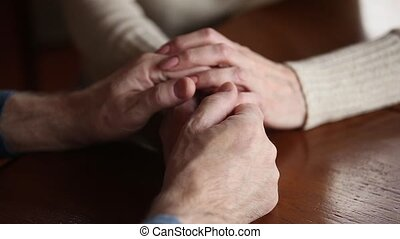 Senior family couple grandparents holding hands expressing...