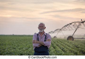 Senior farmer in front of irrigation system
