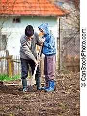 Senior farmer with grandson in the garden