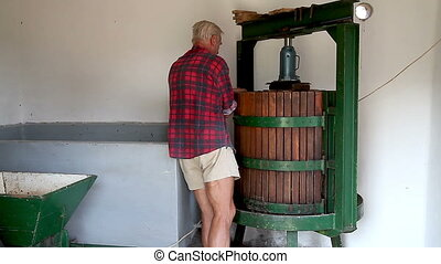 Senior farmer works with the winepress machine