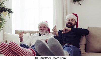 Senior father and adult son sitting on a sofa at Christmas time, having fun.