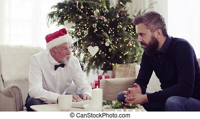 Senior father and adult son sitting on a sofa at Christmas time, talking.