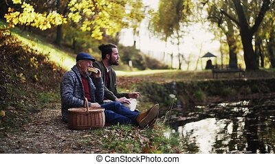 Senior father and his young son sitting by lake in nature, talking and eating. Slow motion.