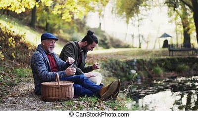 Senior father and his young son sitting by lake in nature, talking and eating.
