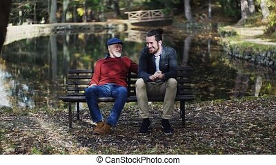 Senior father and his son sitting on bench by lake in...