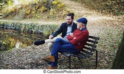 Senior father and his young son sitting on bench by lake in nature, talking. Slow motion.