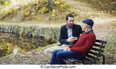 Senior father and his young son sitting on bench by lake in nature, talking.