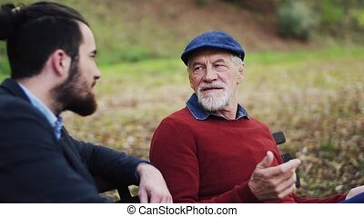 Senior father and his young son sitting on bench in nature, talking.