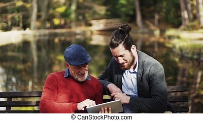 A senior father and his son sitting on bench in nature, using tablet.