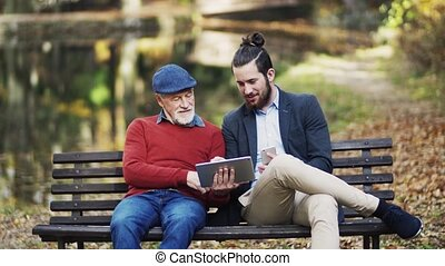 A senior father and his son sitting on bench in nature, using tablet and smartphone.