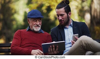A senior father and his son sitting on bench in nature, using tablet and smartphone. Slow motion.