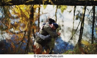 Senior father and his son standing by lake in nature, hugging. Slow motion.