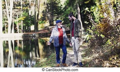 Senior father and his young son walking in nature, talking.