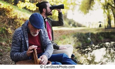 Senior father and his son with binoculars and picninc basket...